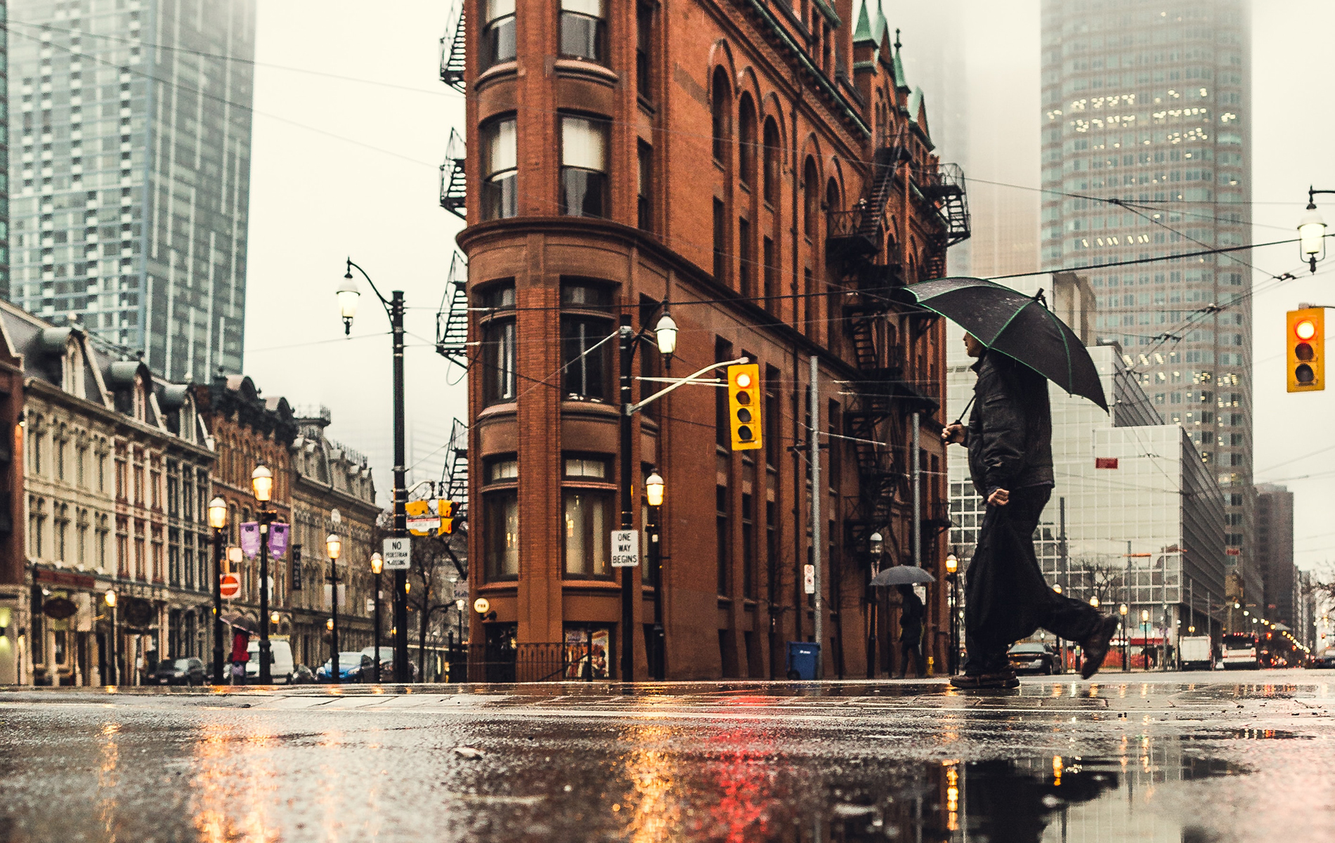Person with umbrella walking across a busy, wet intersection