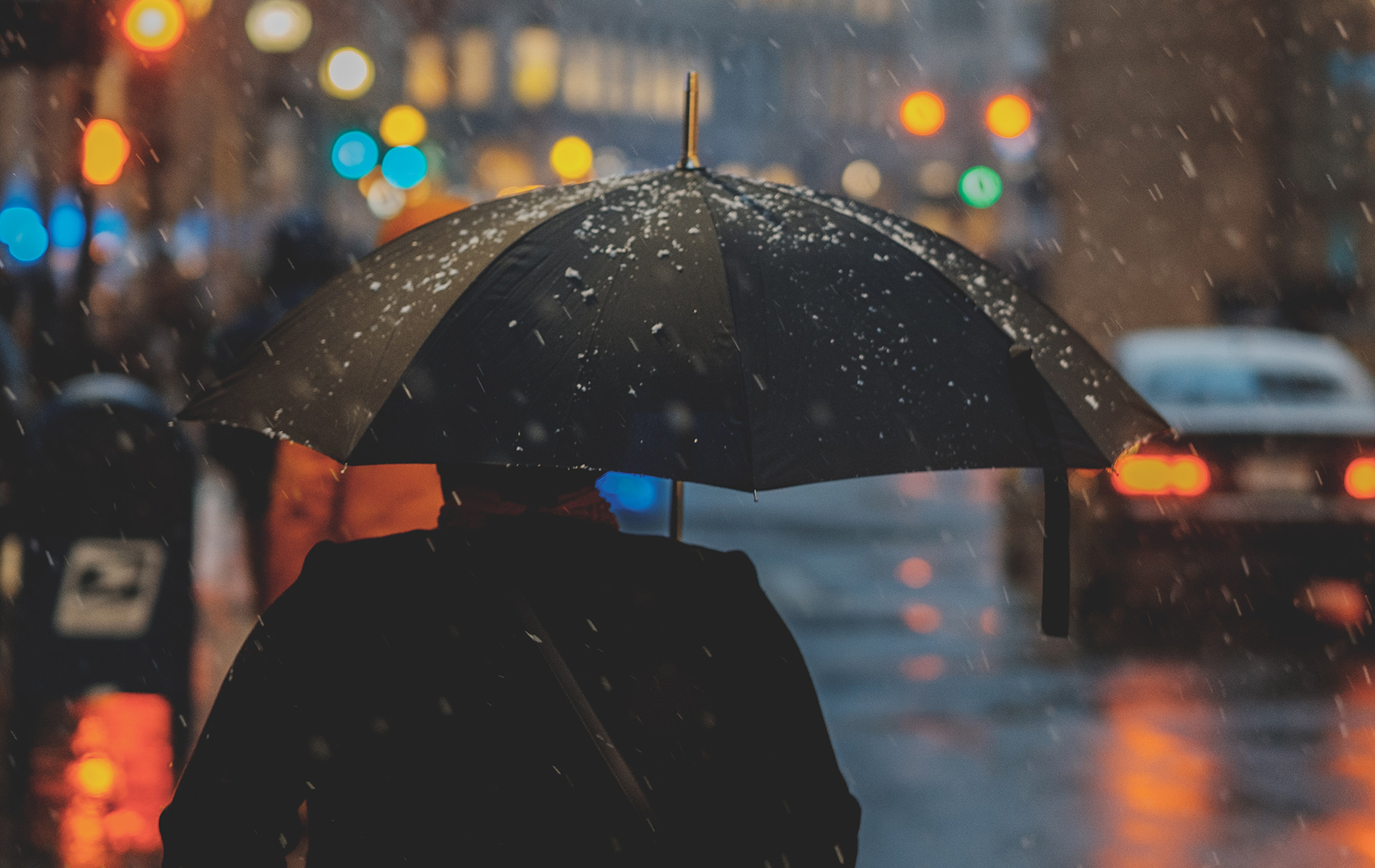 Person with umbrella in the snow at night, looking down a busy street